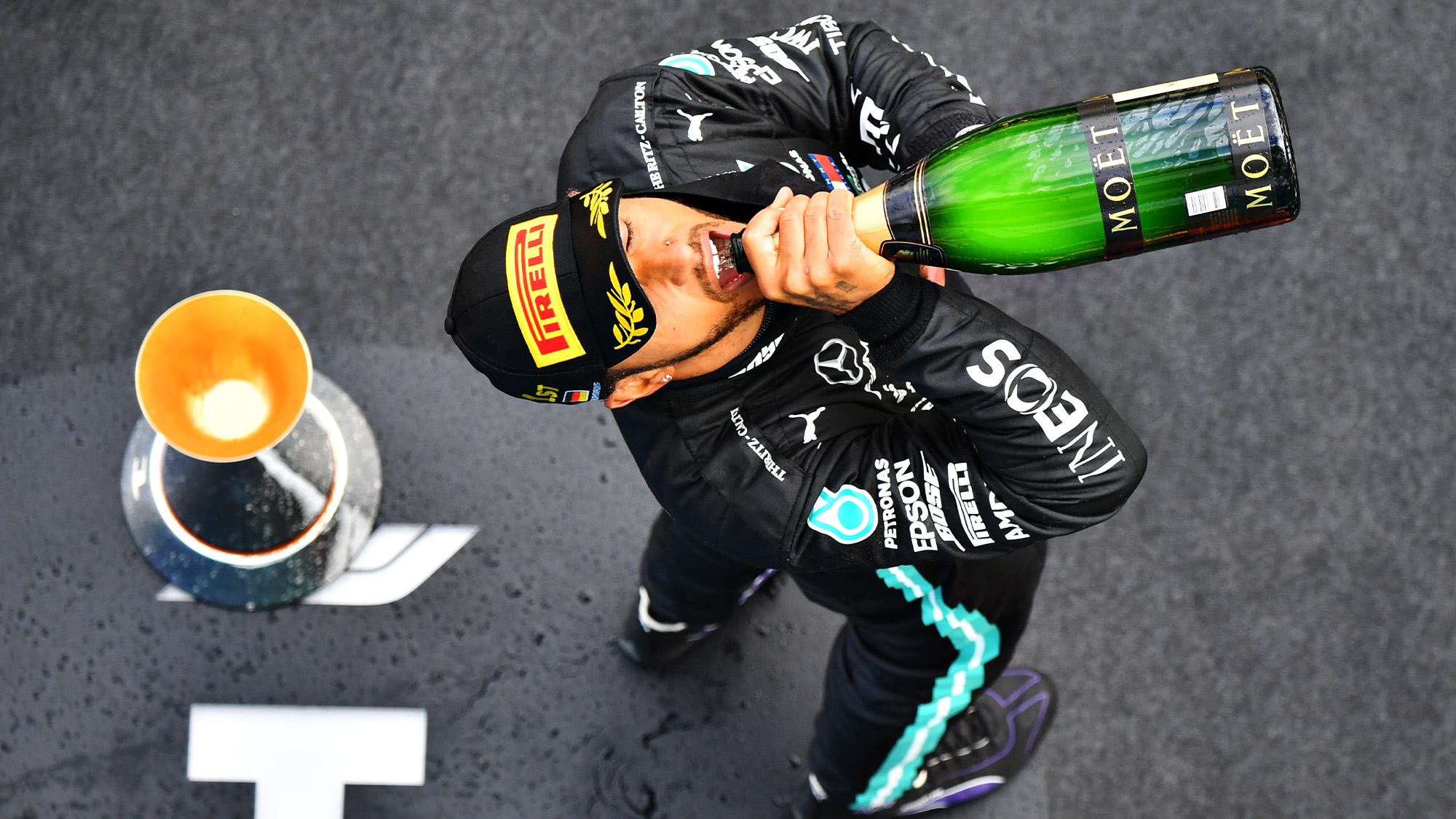 Lewis Hamilton drinks champagne on the podium after winning a record equalling 91st grand prix at the Nurburgring