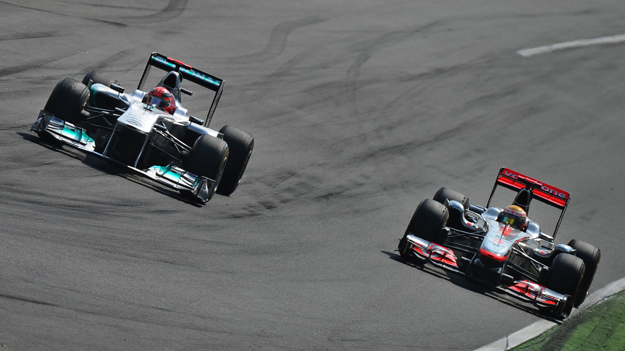 Michael Schumacher and Lewis Hamilton side by side at Monza during the 2011 Italian Grand Prix