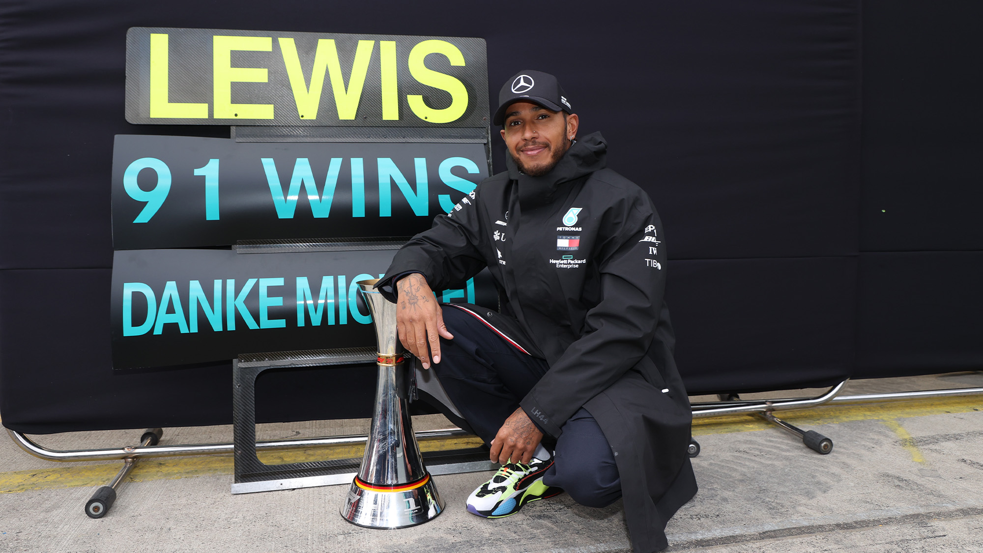 Lewis Hamilton in front of a pitboard marking his record-equalling 91st Formula 1 victory in the 2020 Eifel Grand Prix at the Nurburgring