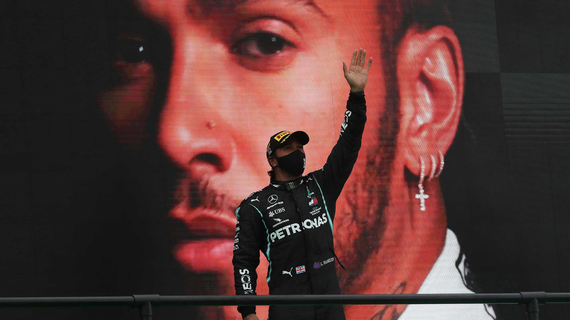 Lewis Hamilton raises his arms in front of a giant picture of himself after winning a record 92nd F1 race at the 2020 Portuguese Grand prix