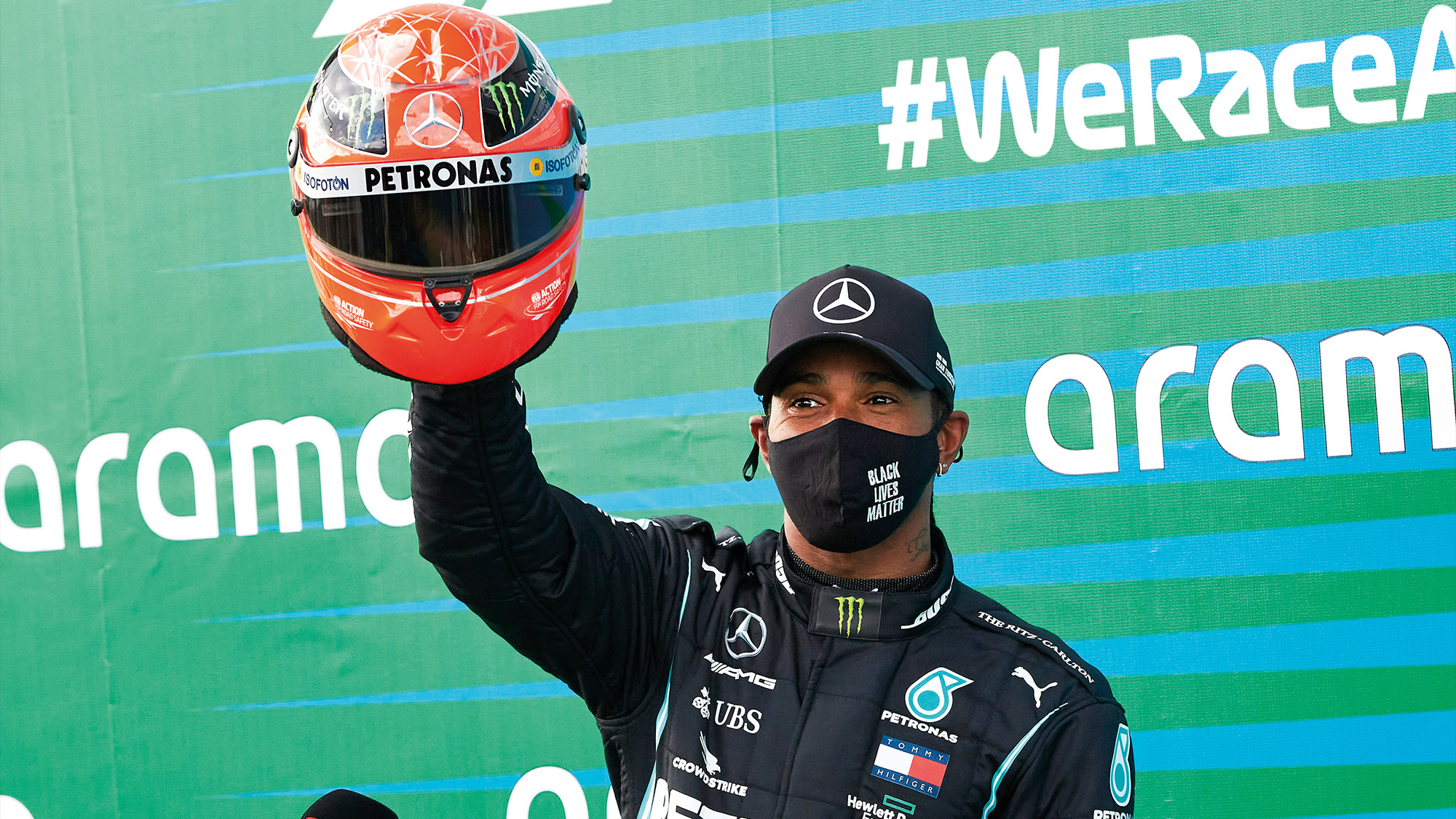 Lewis Hamilton holds up Michael Schumacher's helmet that he was given after equalling the record for the number of F1 wins atthe 2020 Eifel Grand prix