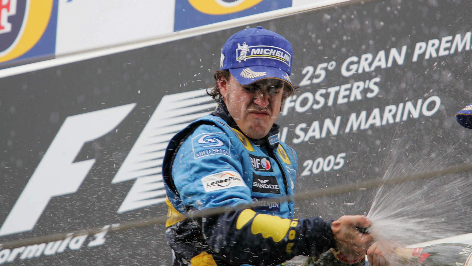 FErnando Alonso celebrates winning the 2005 San MArino Grand Prix with champagne on the podium at Imola