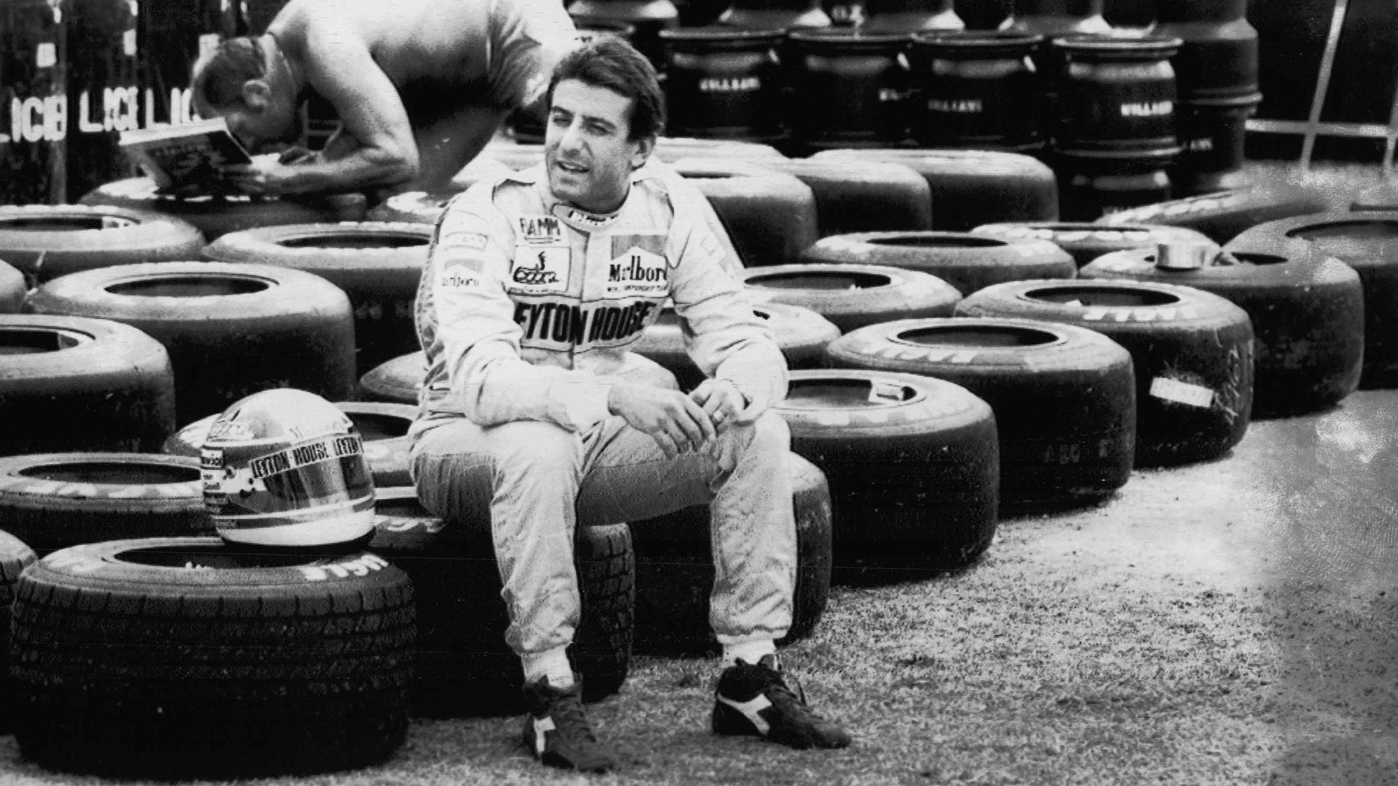 Ivan Capelli sits on tyres in his Leyton House overalls