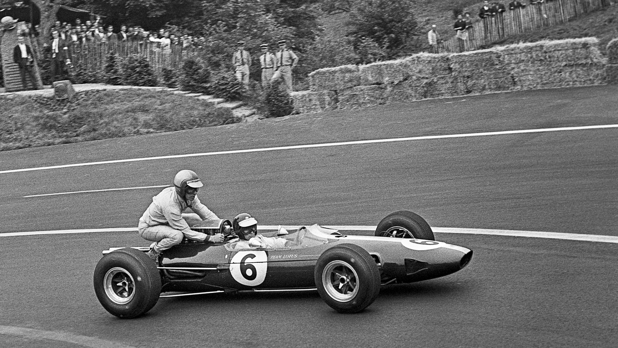 Jim Clark gives Mike Spence a lift to the pits on the back of his Lotus 25 at the 1965 French Grand Prix