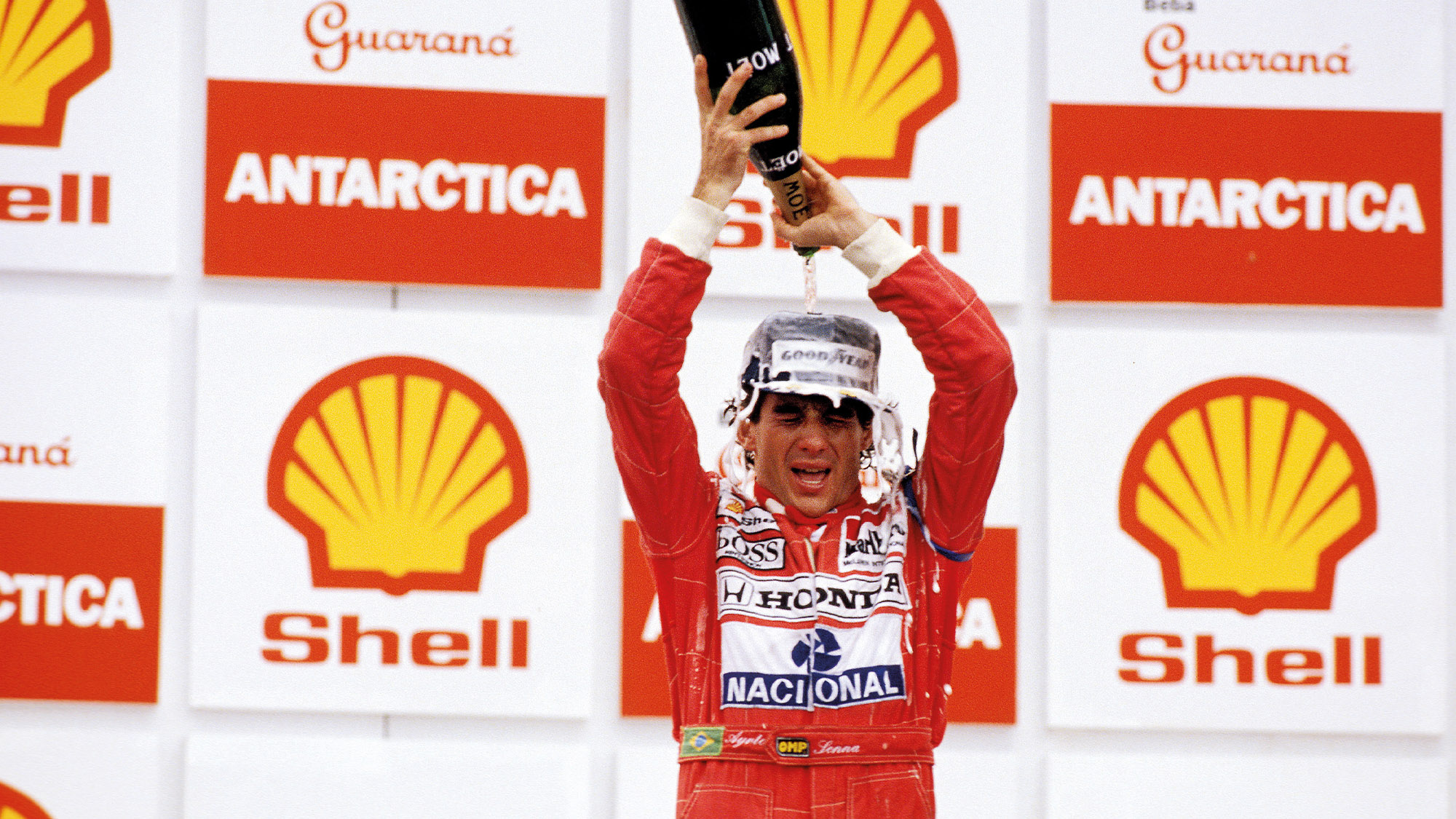 Ayrton Senna pours champagne over his head after winning the 1991 Brazilian Grand PRix at Interlagos for McLaren