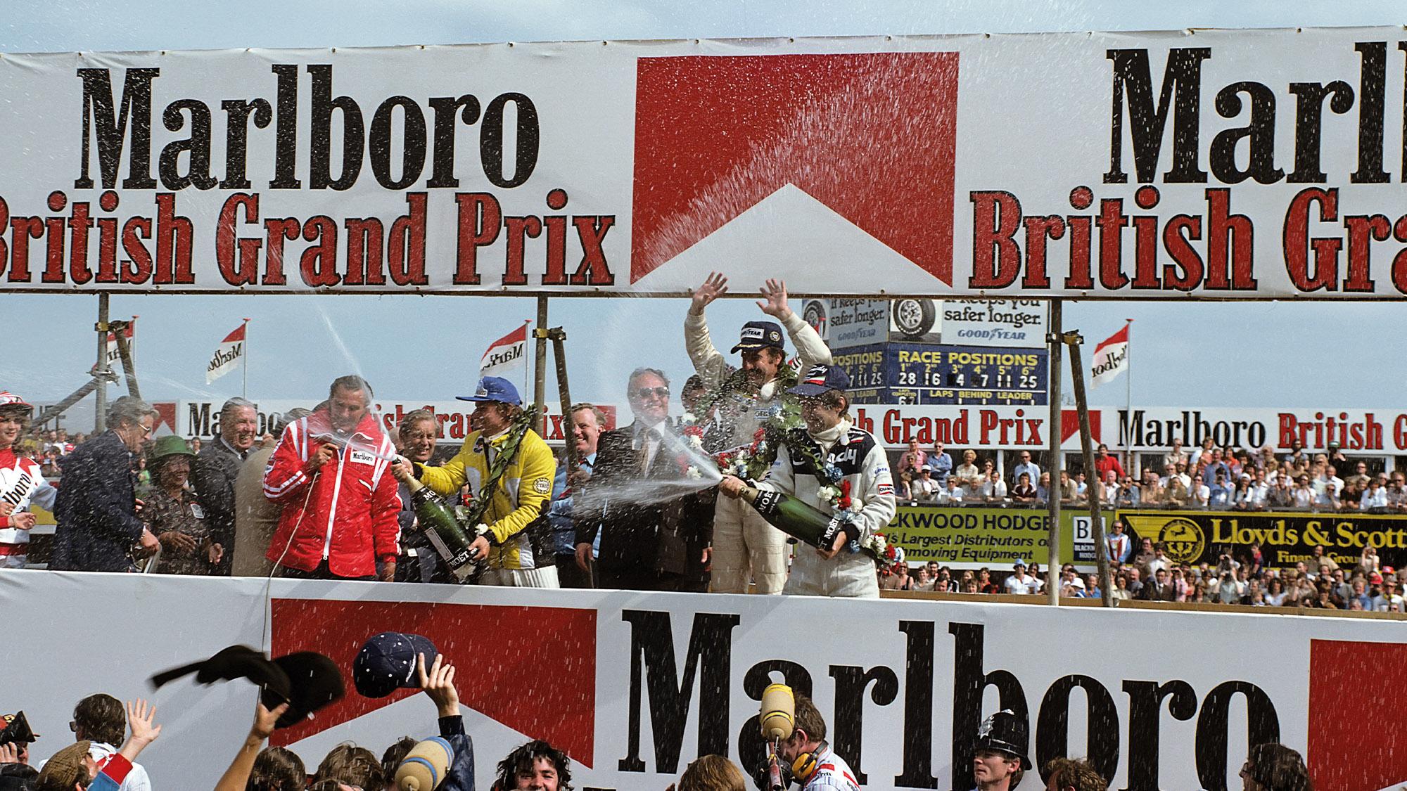 Clay Regazzoni celebrates Williams' forst win on the Silverstone podium at the 1979 British Grand Prix