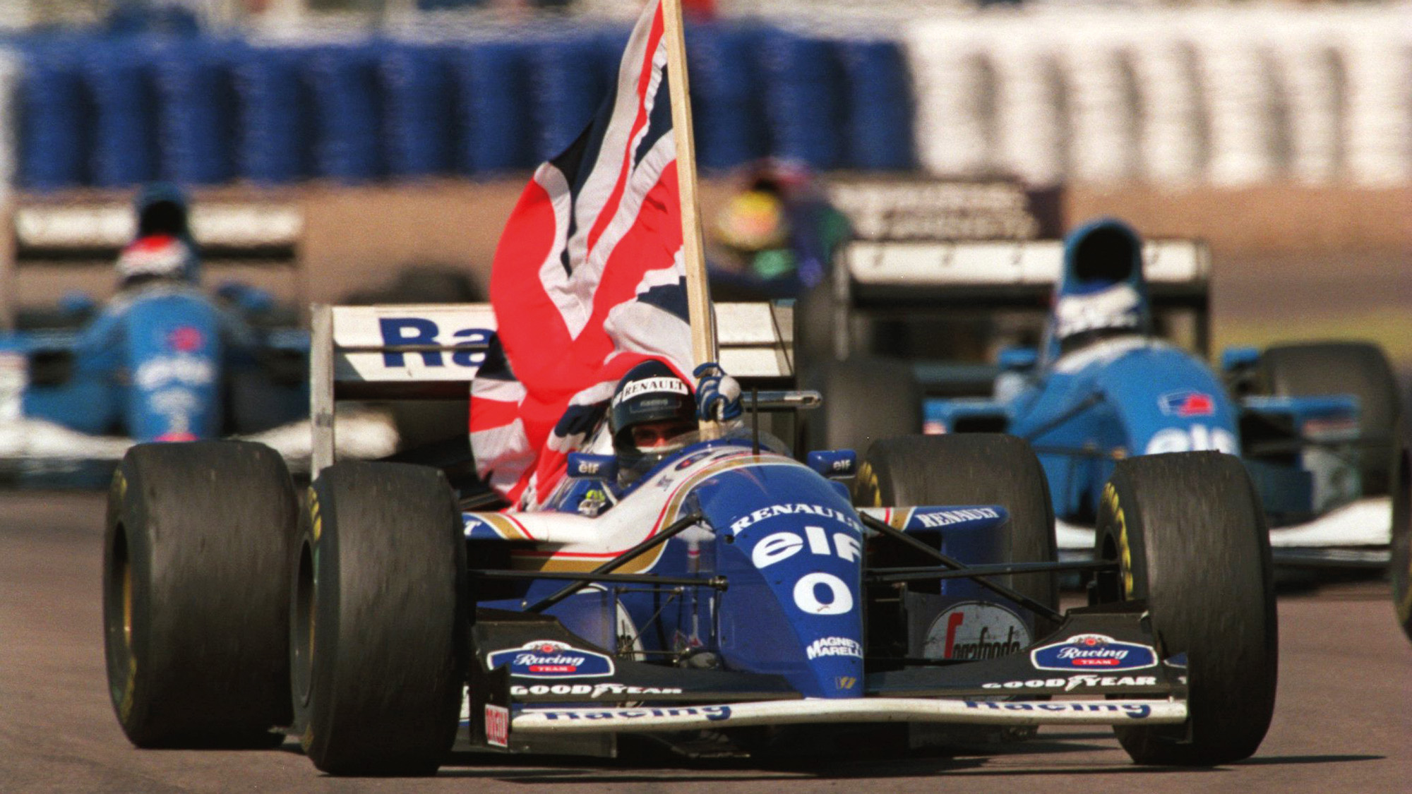Damon Hill holds a Union flag in his Williams after winning the 1994 British Grand Prix at Silverstone