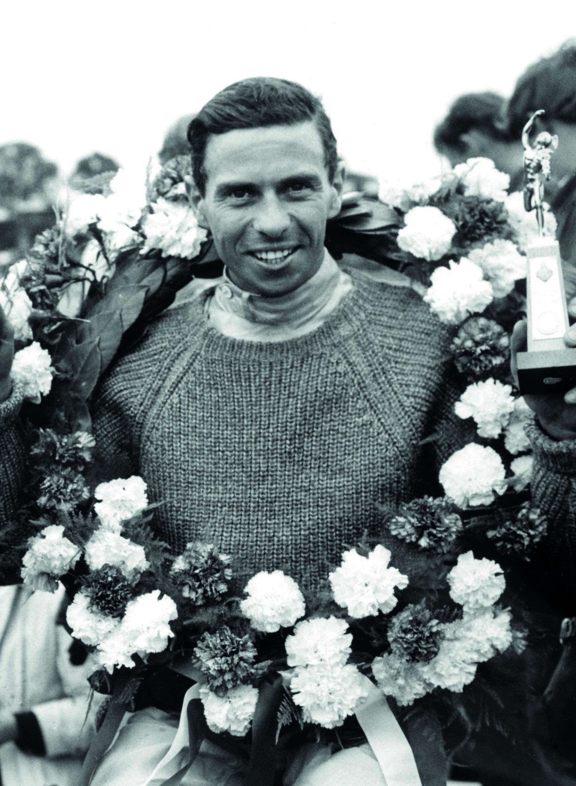 Jim-Clark-celebrates-winning-the-1965-British-Grand-Prix-at-Silverstone-with-a-garland-around-his-neck