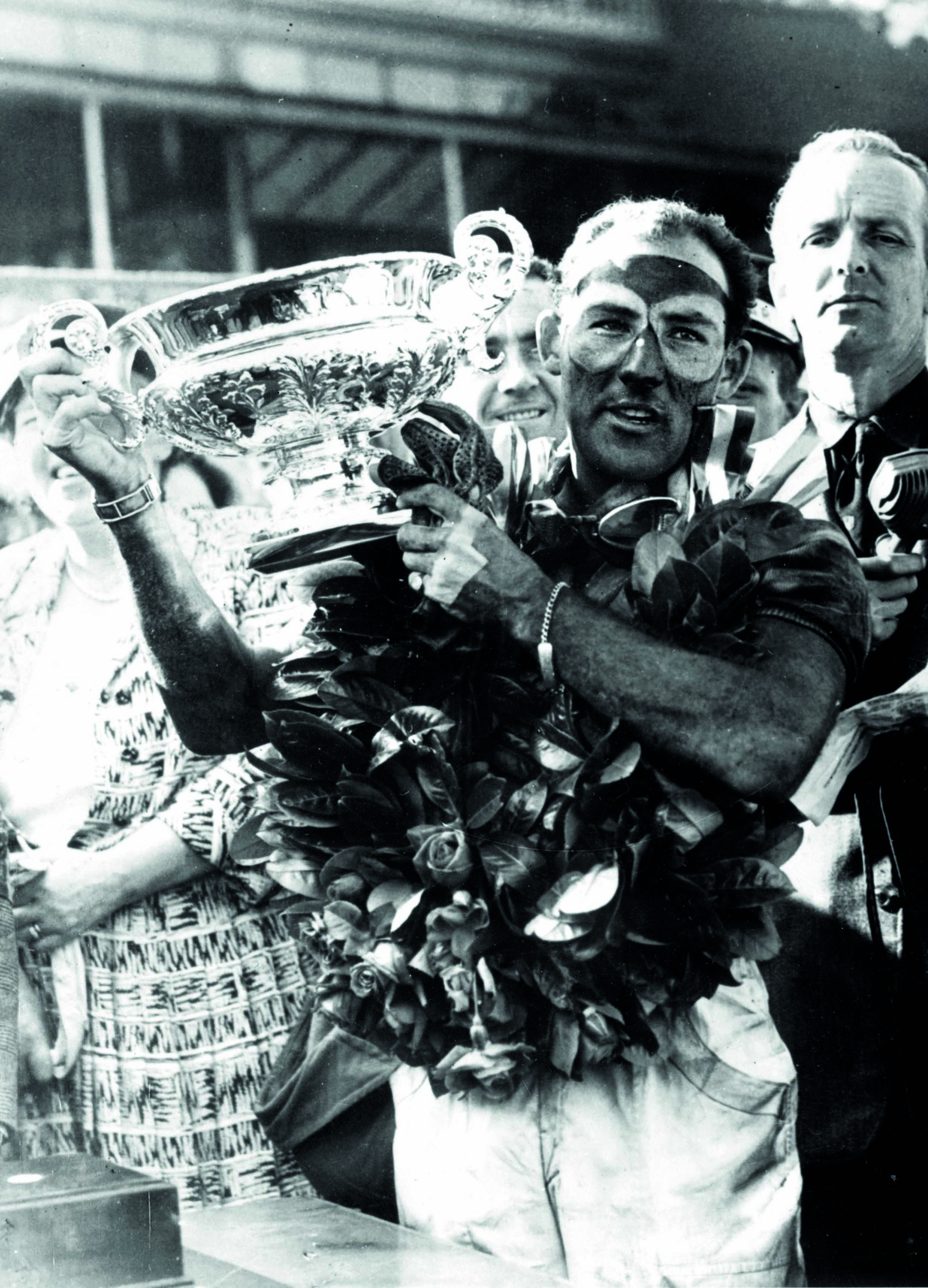 Stirling-Moss-raises-the-winning-trophy-from-the-1955-British-Grand-Prix-at-Aintree