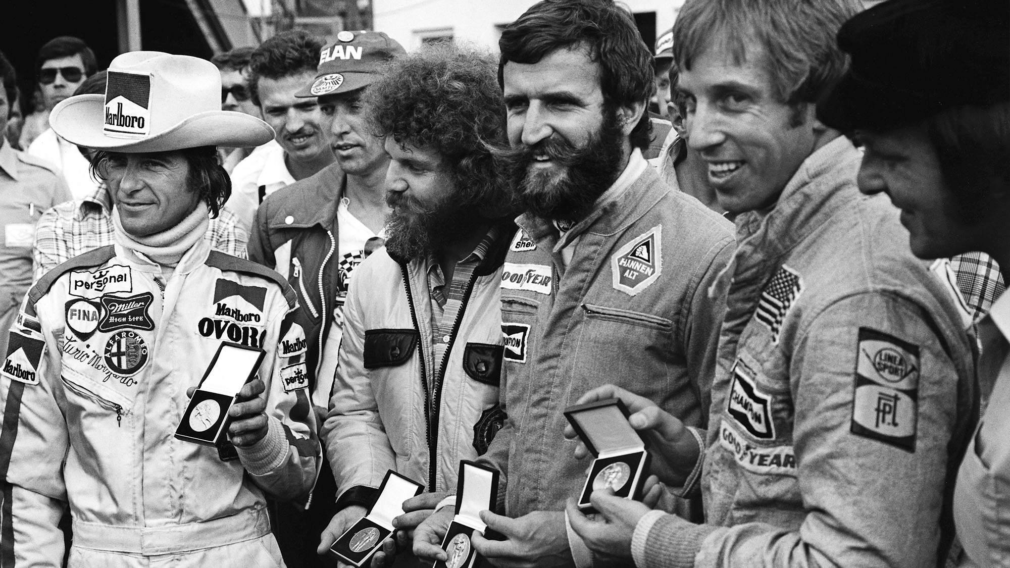 Arturo Merzario receives a medal for helping to save Niki Lauda's life along with a representative of Guy Edwards, Harald Ertl and Brett Lunger