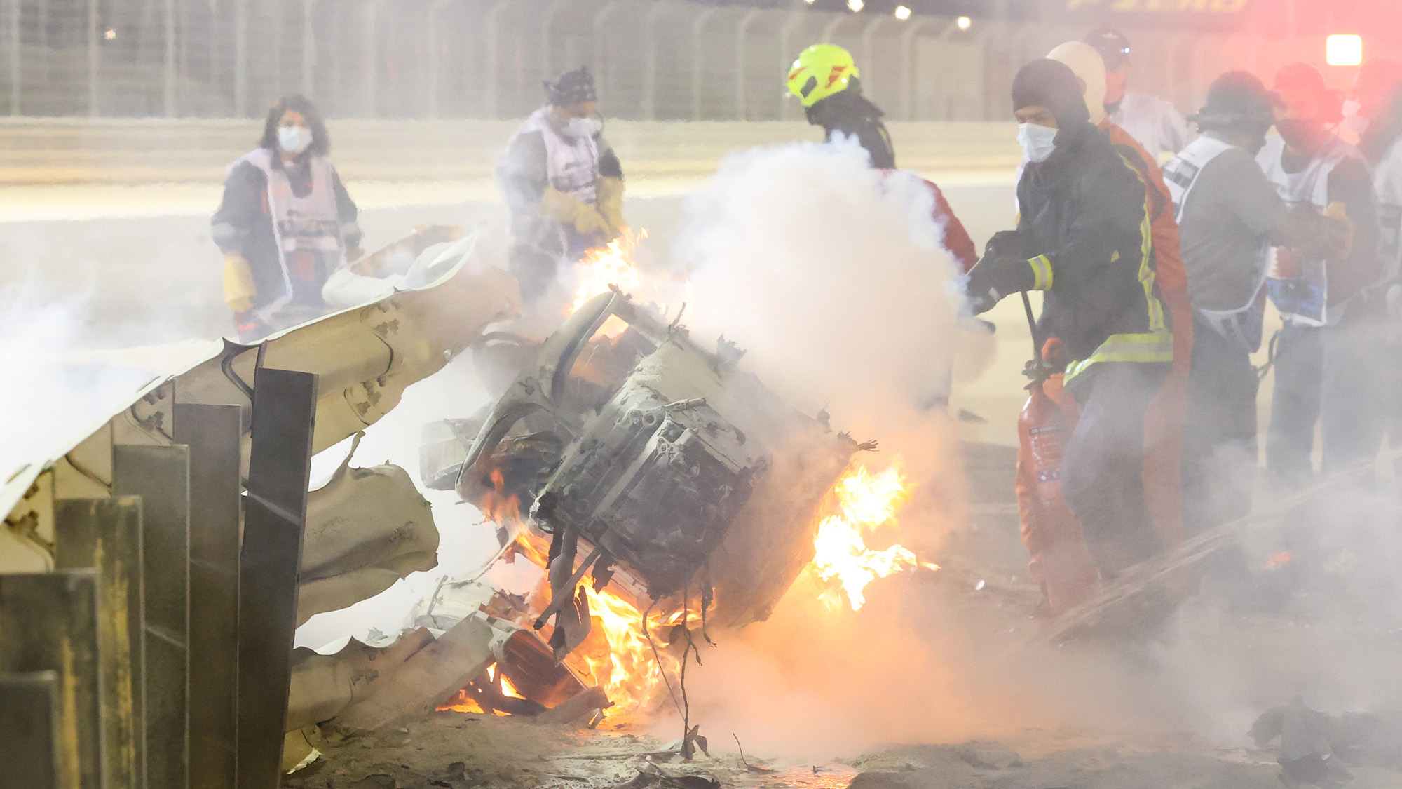 The front part of Romain Grosjean's wrecked Haas on fire and embedded in the barrier