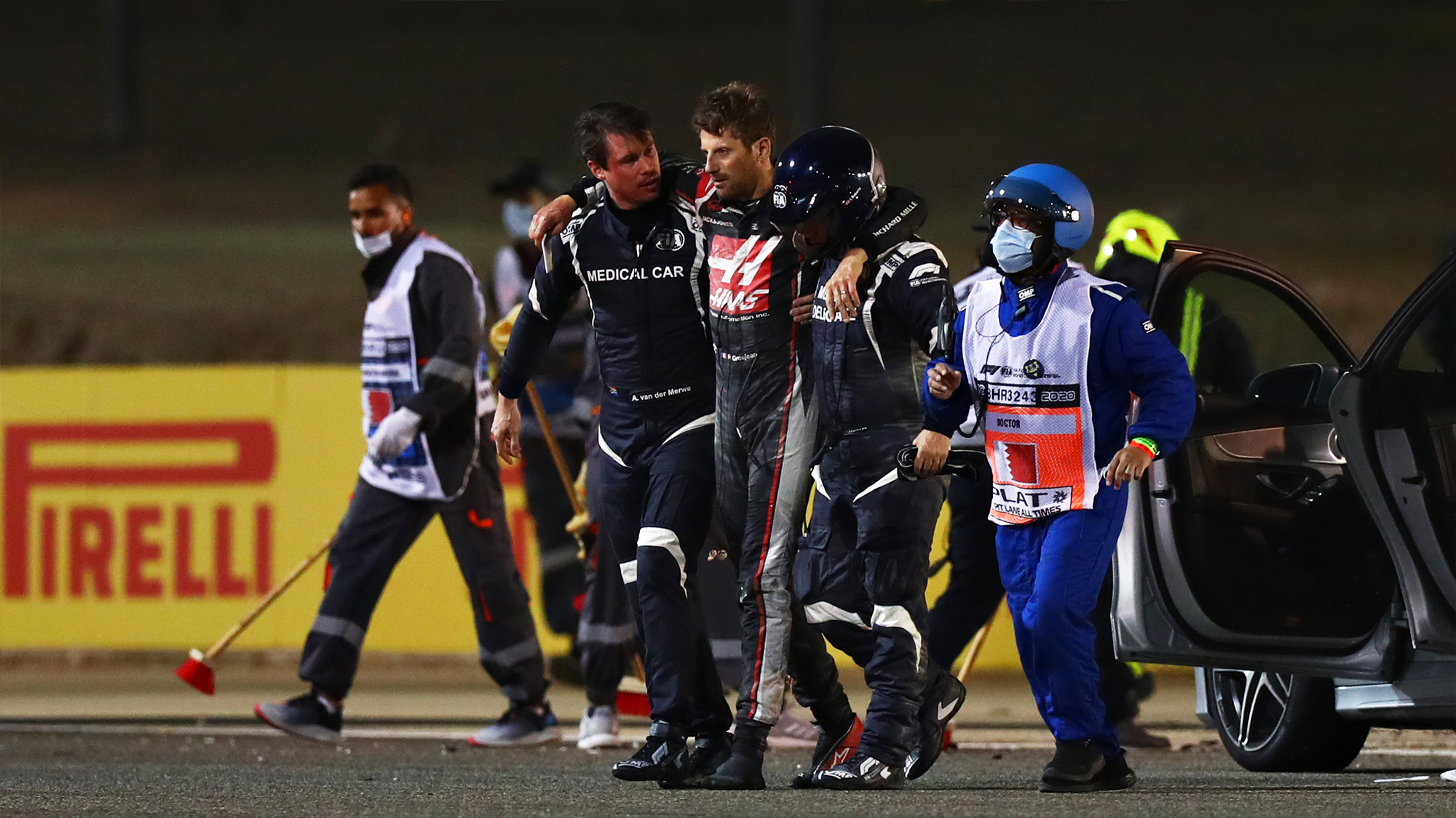Romain Grosjean is lead away from the burnt wreckage of his car after crashing at the 2020 F1 Bahrain Grand Prix