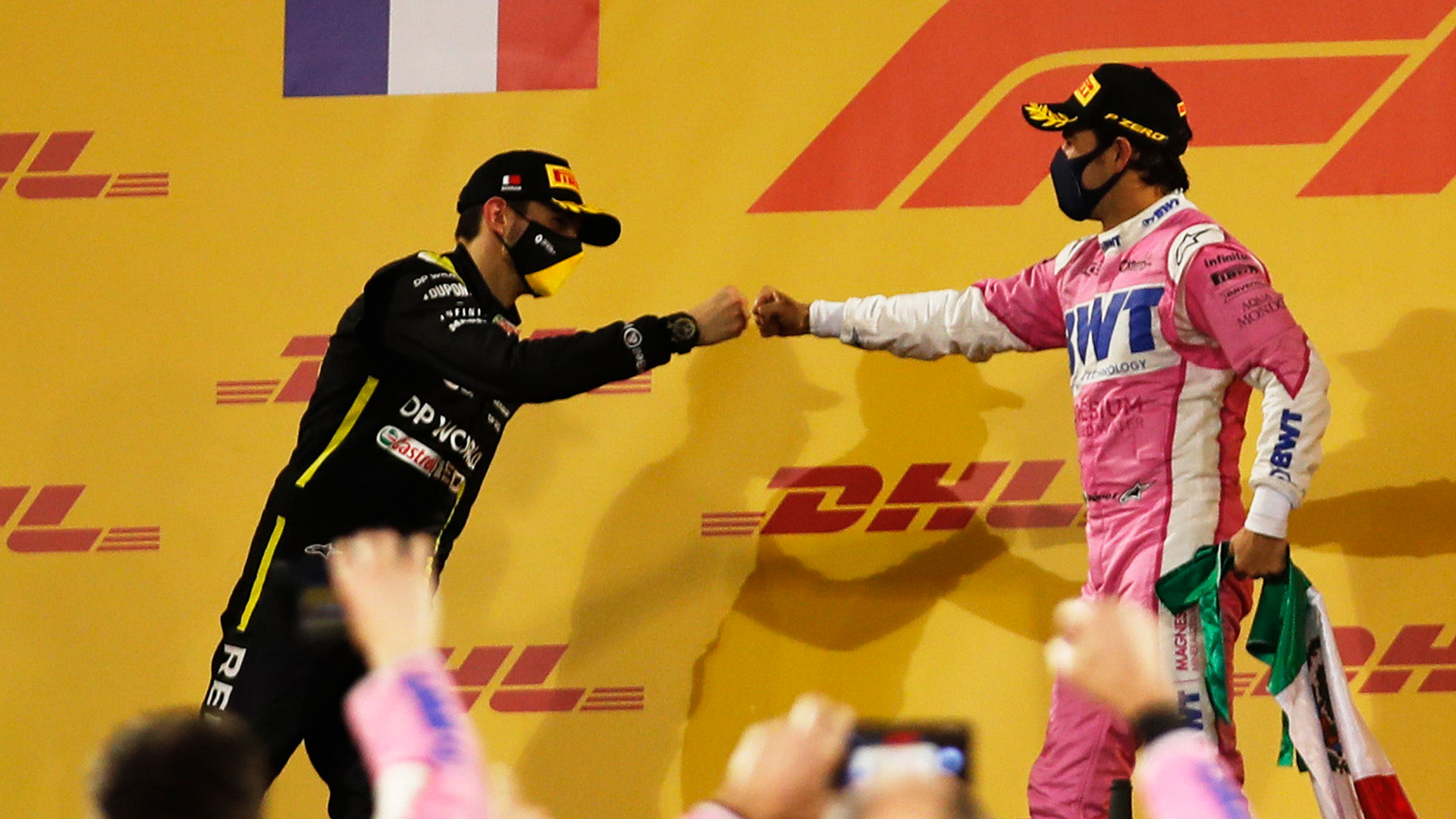 Sergio Perez manages a fist bump with Esteban Ocon on the podium after the 2020 Sakhir Grand Prix