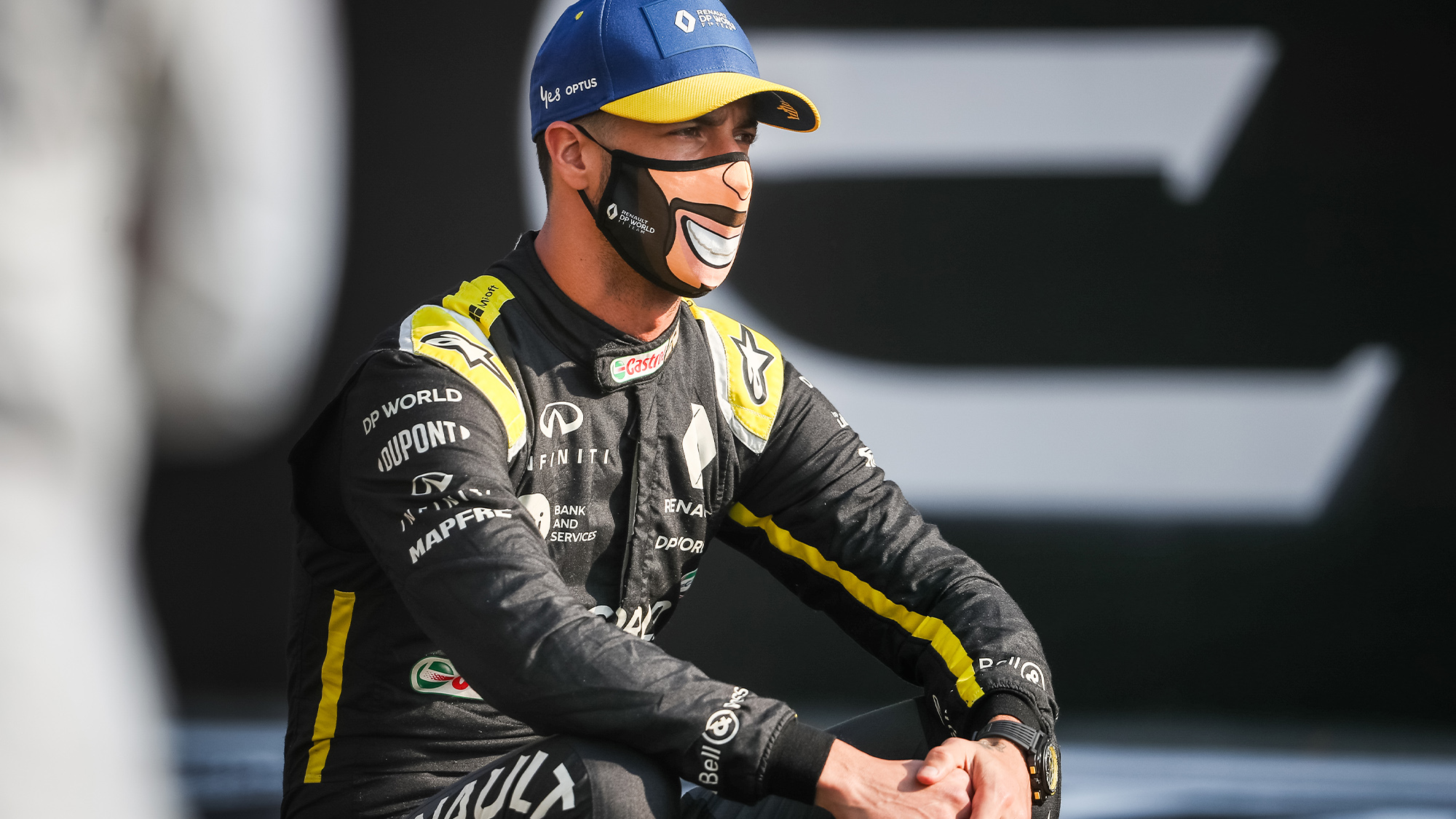 Daniel Ricciardo wears a face mask showing a big smile