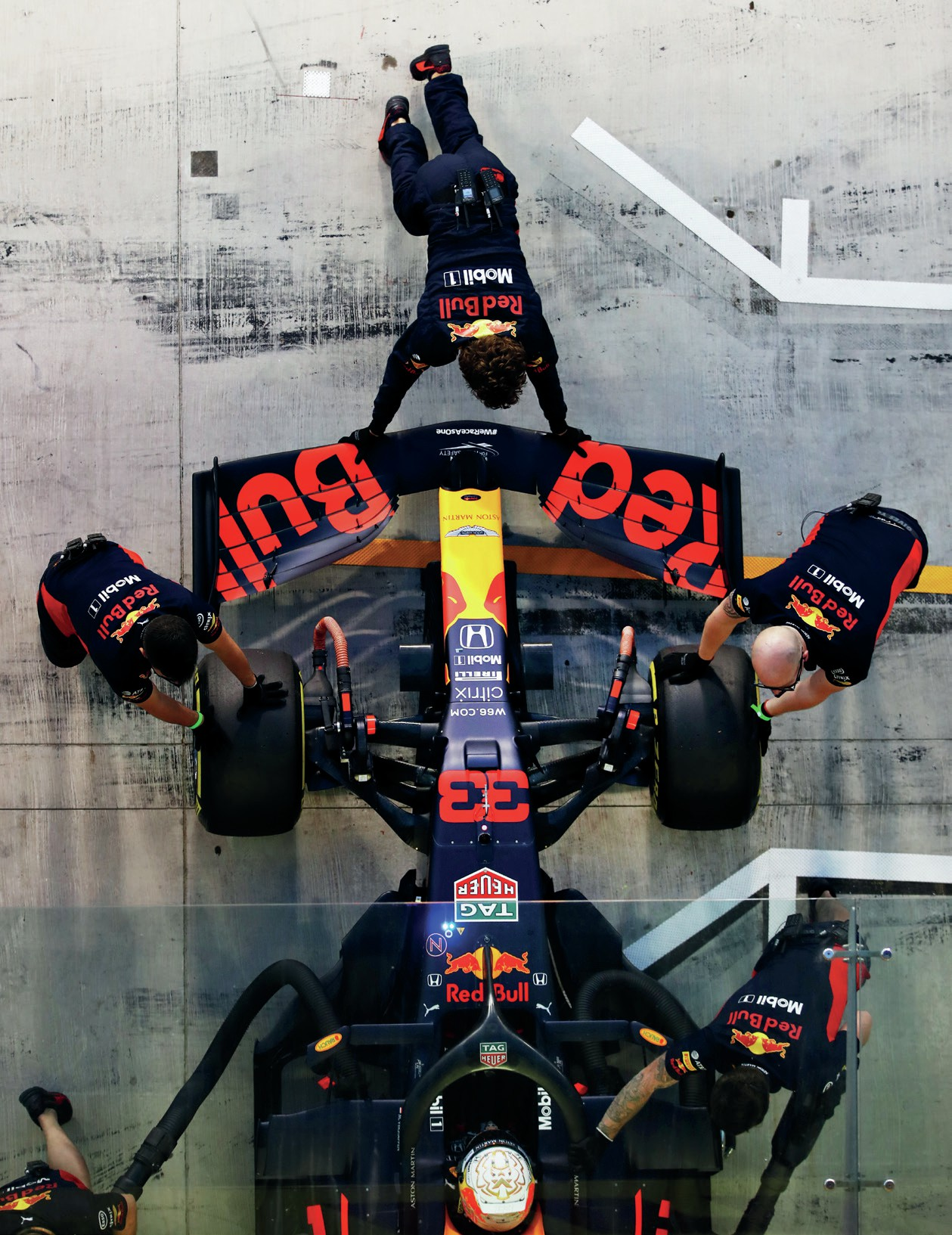 Red Bull of Max Verstappen is pushed into the pit garage