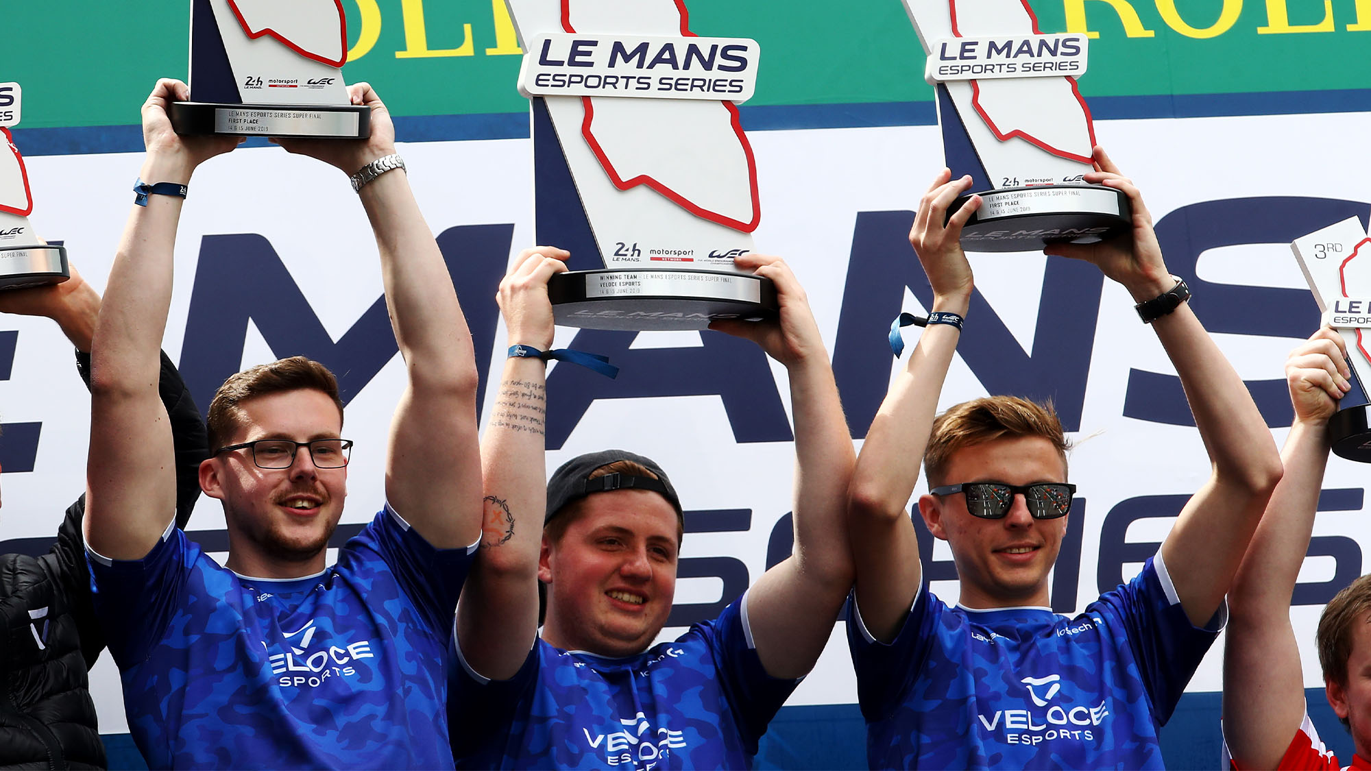 LE MANS, FRANCE - JUNE 15: (L-R) David Kelly (Sauber Dave) , Noah Schmitz (Veloce Virus) and James Baldwin (Veloce Jaaames) of Team Veloce celebrate on the podium after winning the Le Mans Esports Series Super Finale in the Fan Zone at the Circuit de la Sarthe on June 15, 2019 in Le Mans, France. (Photo by Ker Robertson/Getty Images)