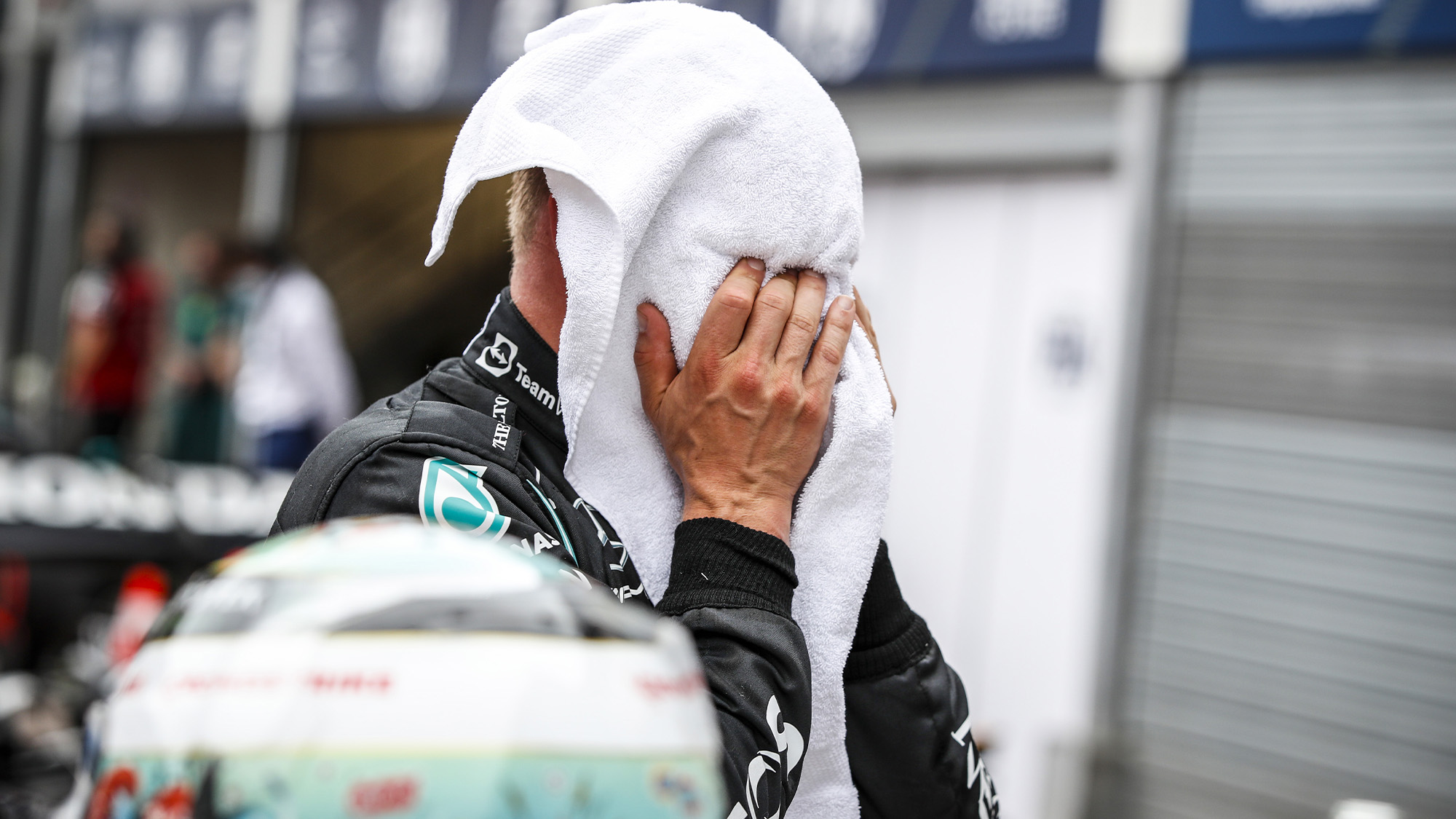 Valtteri Bottas with his face in a towel after 2021 Monaco GP qualifying