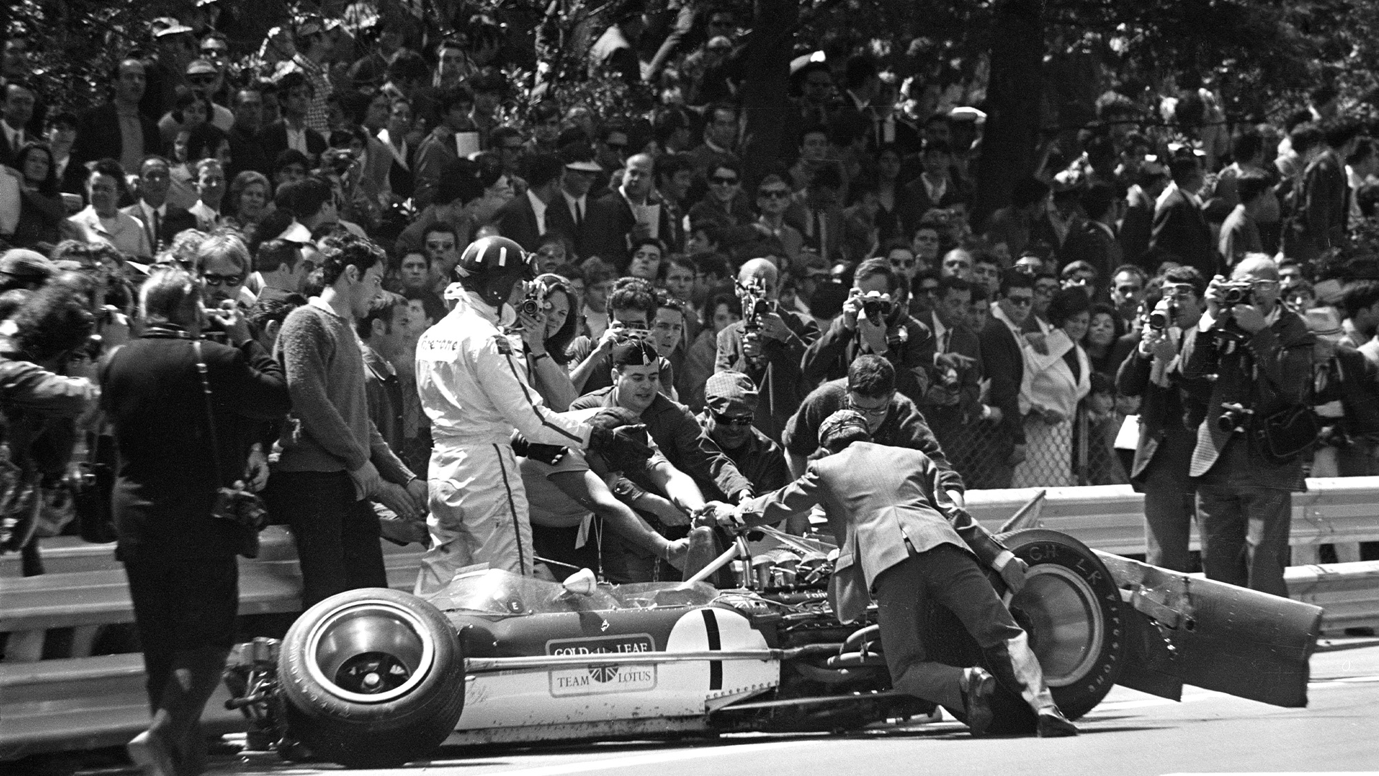 Graham Hill and his crashed Lotus at Montjuich Park in 1969