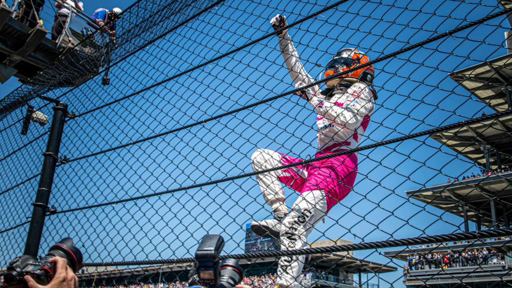 Helio Castroneves climbs the fence after winning the 2021 Indy 500
