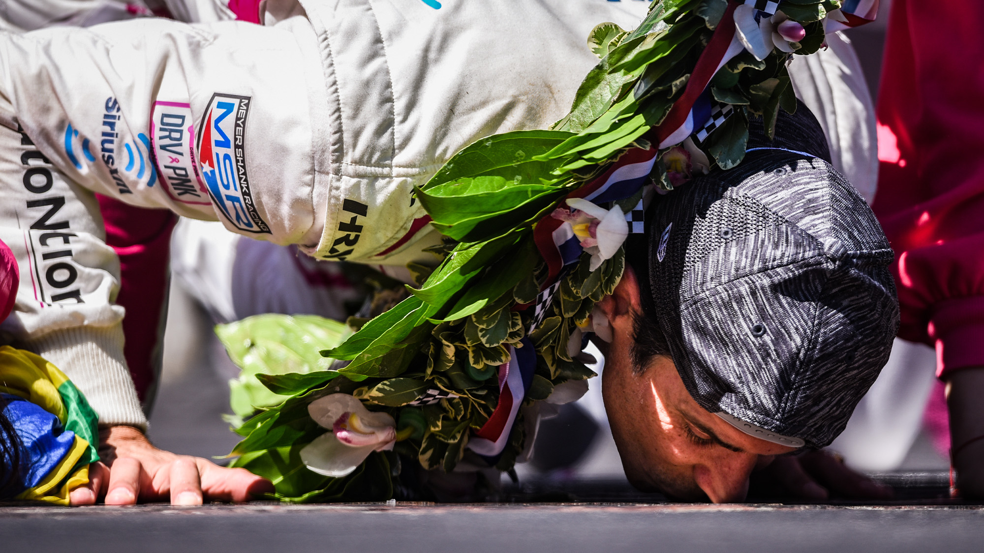 Helio Castroneves kisses the bricks after winning the 2021 Indy 500