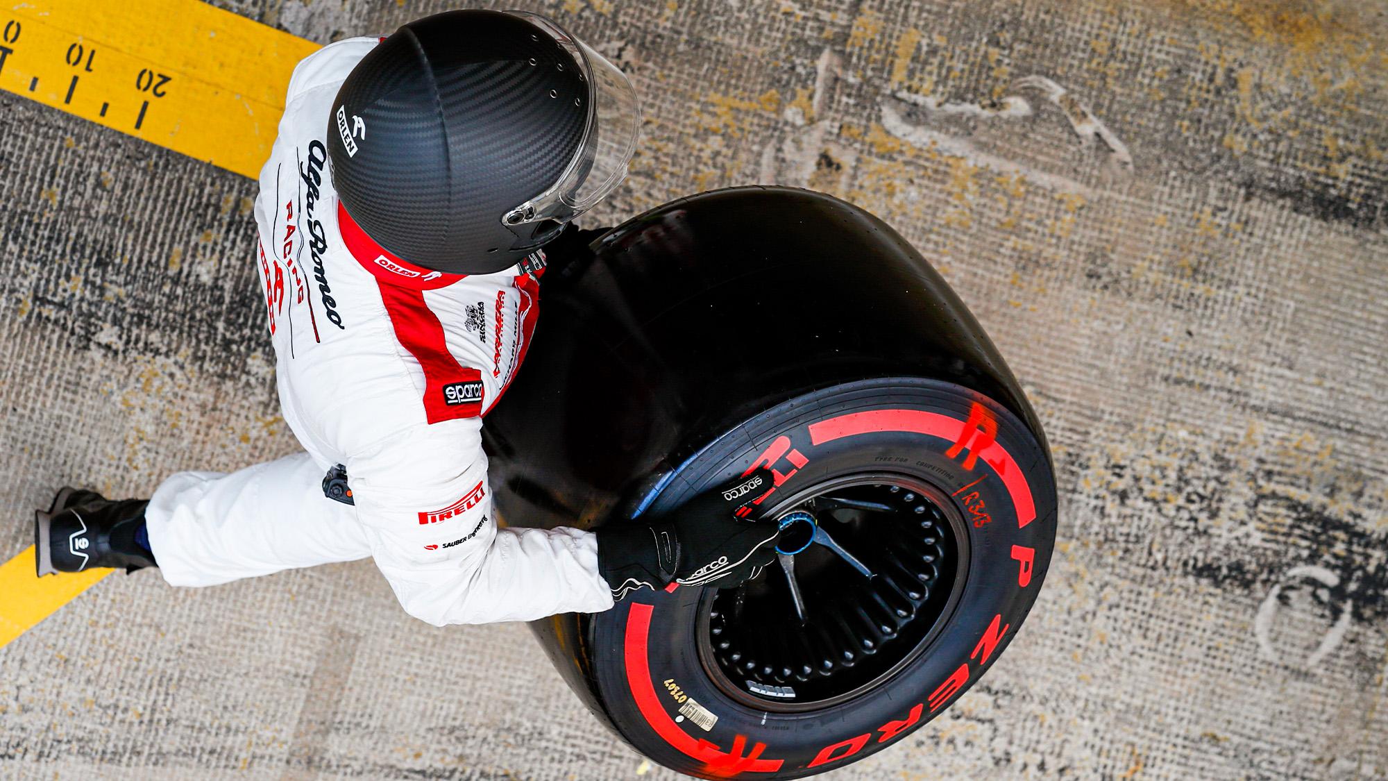 F1 mechanic carries a Pirelli tyre