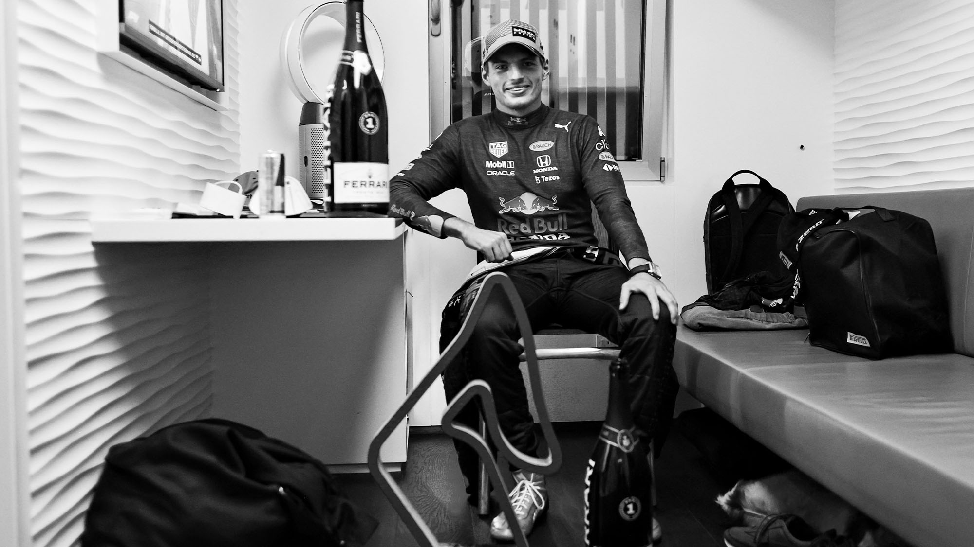 SPIELBERG, AUSTRIA - JUNE 27: (EDITORS NOTE: Image has been converted to black and white.) Race winner Max Verstappen of Netherlands and Red Bull Racing relaxes with his trophy and sparkling wine after the F1 Grand Prix of Styria at Red Bull Ring on June 27, 2021 in Spielberg, Austria. (Photo by Mark Thompson/Getty Images)