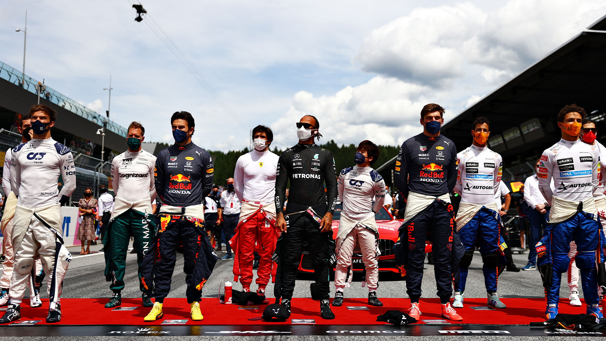 SPIELBERG, AUSTRIA - JUNE 27: Pierre Gasly of France and Scuderia AlphaTauri, Sebastian Vettel of Germany and Aston Martin F1 Team, Sergio Perez of Mexico and Red Bull Racing, Carlos Sainz of Spain and Ferrari, Yuki Tsunoda of Japan and Scuderia AlphaTauri, Lewis Hamilton of Great Britain and Mercedes GP, Max Verstappen of Netherlands and Red Bull Racing, Daniel Ricciardo of Australia and McLaren F1 and Lando Norris of Great Britain and McLaren F1 stand for the national anthem on the grid ahead of the F1 Grand Prix of Styria at Red Bull Ring on June 27, 2021 in Spielberg, Austria. (Photo by Dan Istitene - Formula 1/Formula 1 via Getty Images)