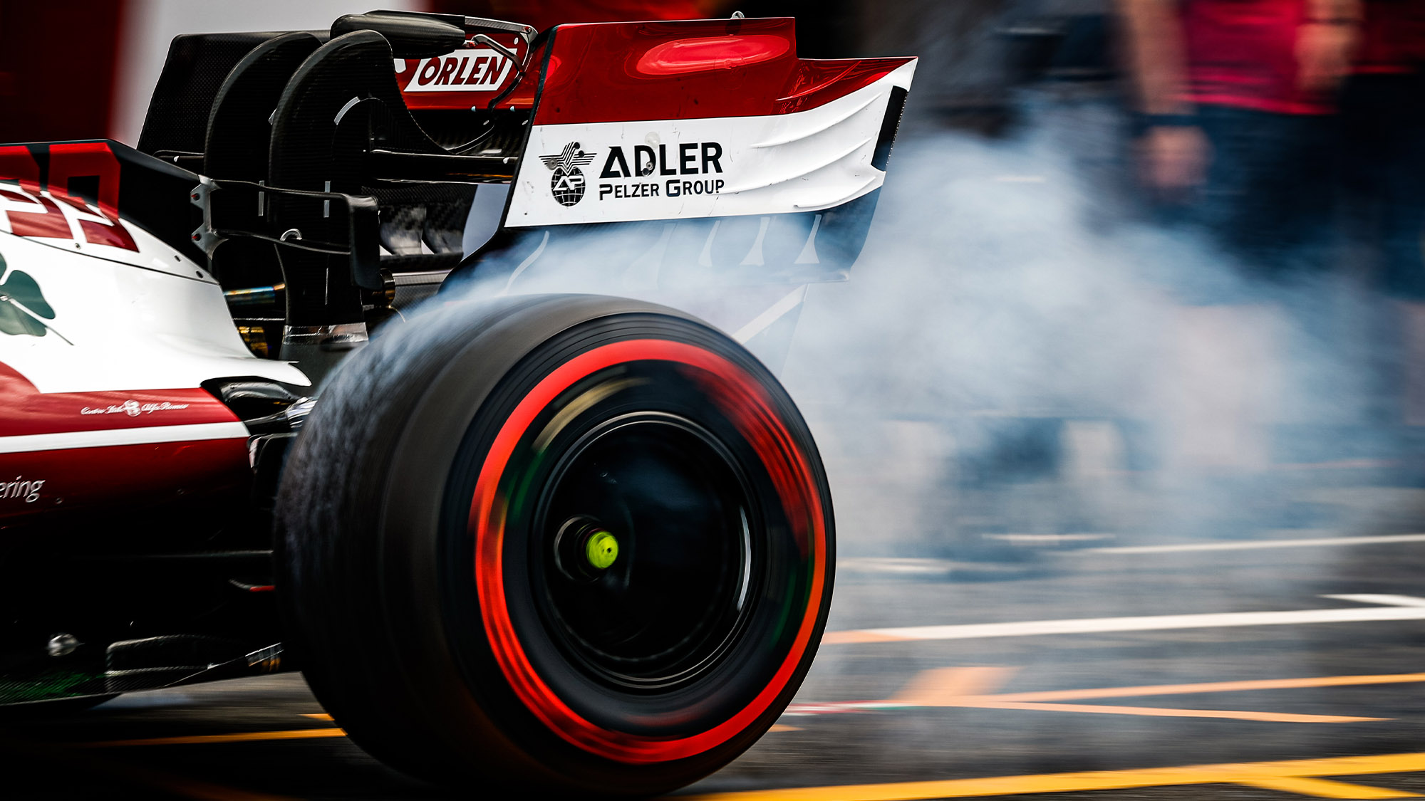 Smoke comes off the spinning soft F1 tyre of an Alfa Romeo