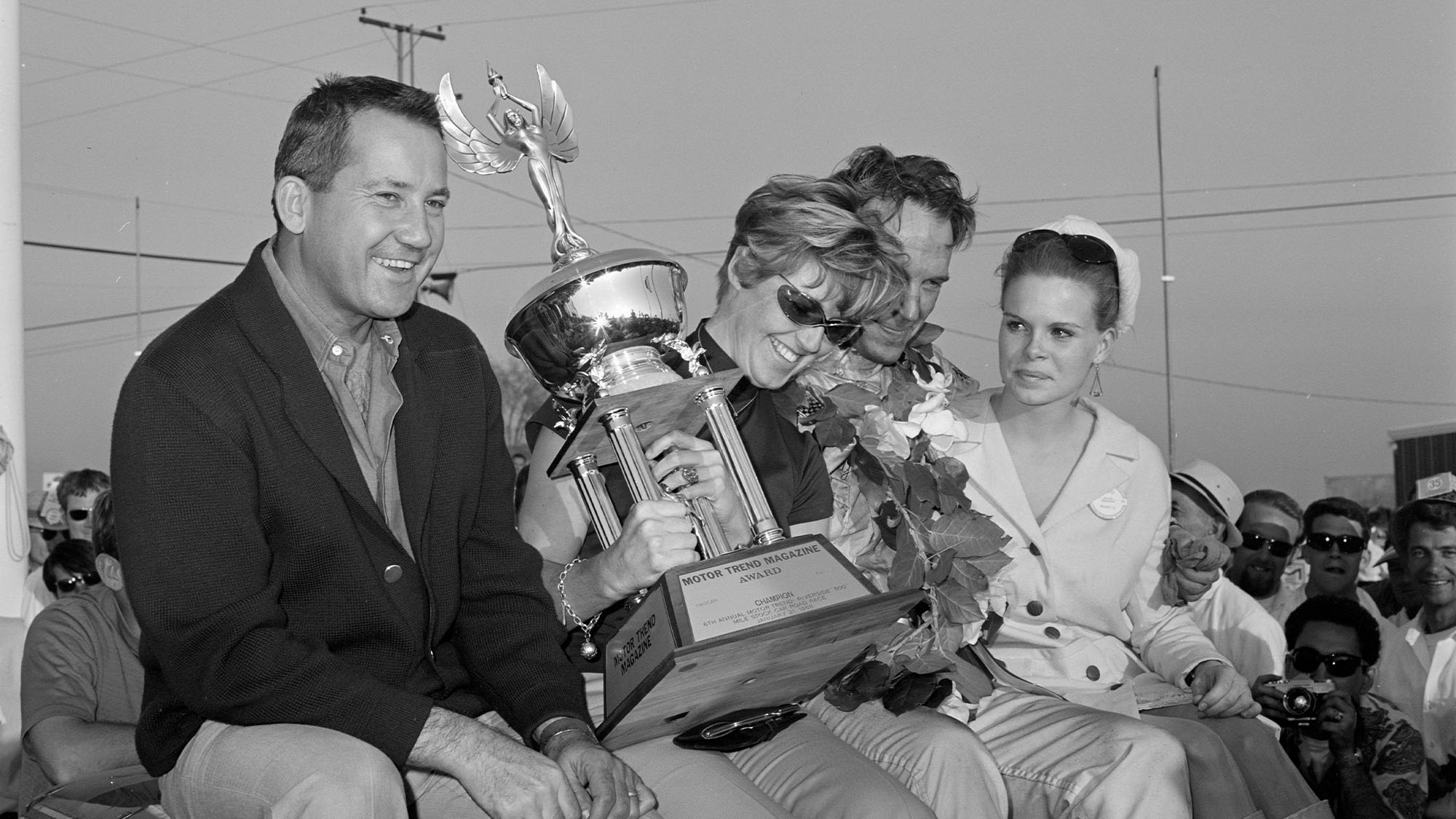 UNITED STATES - JANUARY 22: 1968 Motor Trend 500 - Riverside - NASCAR. Race winner Dan Gurney celebrates his victory with Race queen far right and Petersen Publishing founder Robert E. Petersen (left). (Photo by Eric Rickman/The Enthusiast Network via Getty Images/Getty Images)