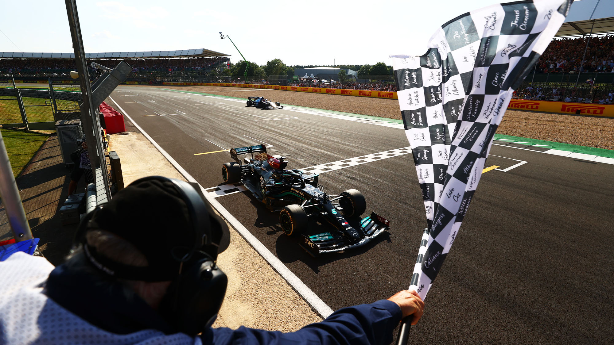 NORTHAMPTON, ENGLAND - JULY 18: Race winner Lewis Hamilton of Great Britain driving the (44) Mercedes AMG Petronas F1 Team Mercedes W12 takes the chequered flag during the F1 Grand Prix of Great Britain at Silverstone on July 18, 2021 in Northampton, England. (Photo by Dan Istitene - Formula 1/Formula 1 via Getty Images)